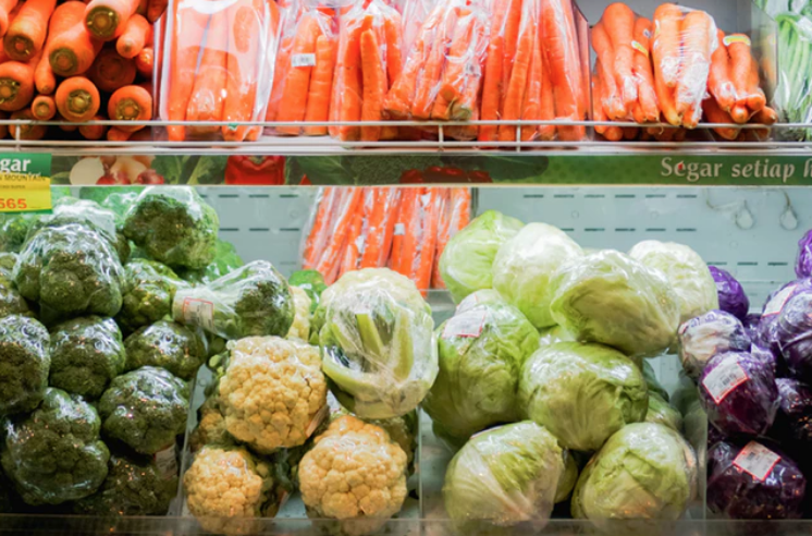 refrigerated shelf in supermarket with an array of vegetables including cauliflower, carrots, broccoli and cabbage.