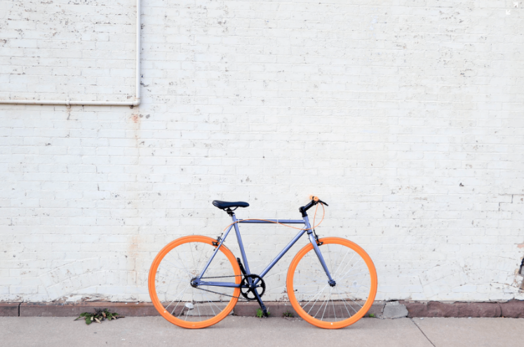 blue bike with orange wheels against a white wall