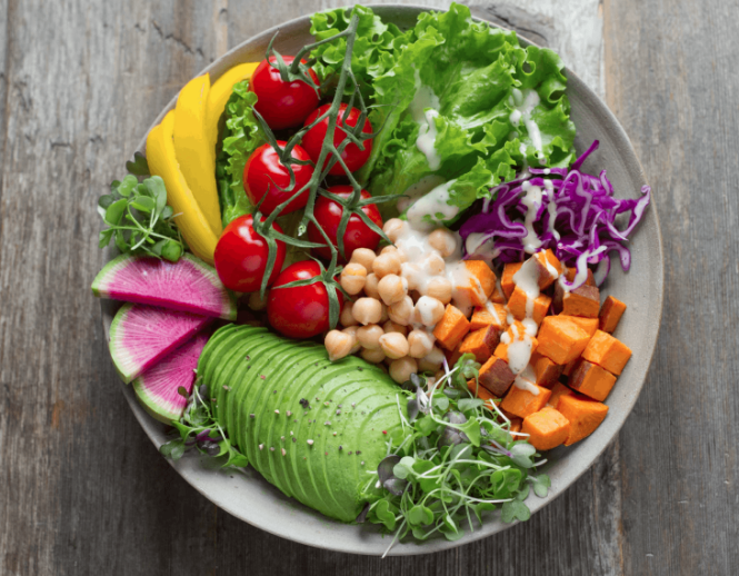 high fibre, colourful salad bowl with tomatoes, avocado, chickpeas, sweet potato, cabbage and lettuce.