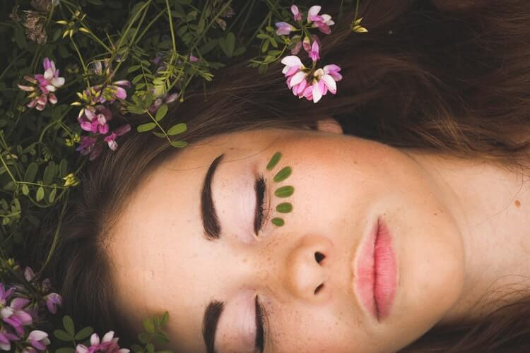 pretty girl lay on top of some shrubbery with her eyes closed and leaves under her eyes