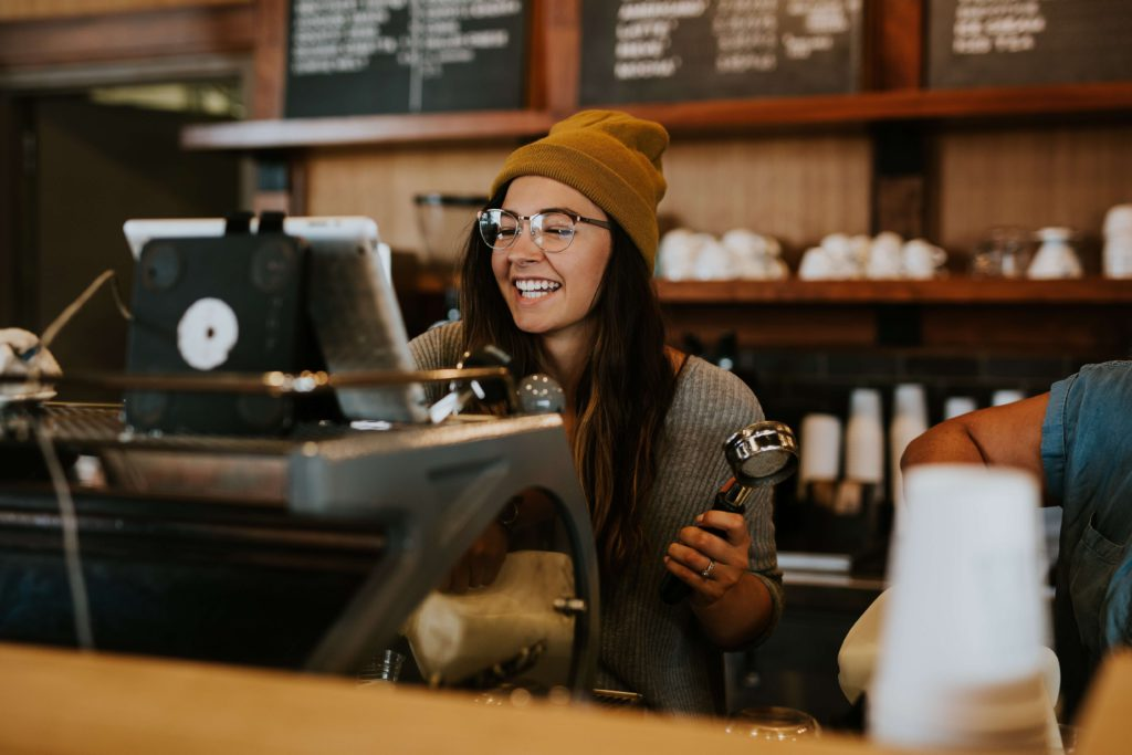 smiling female barista behind a coffee  machine