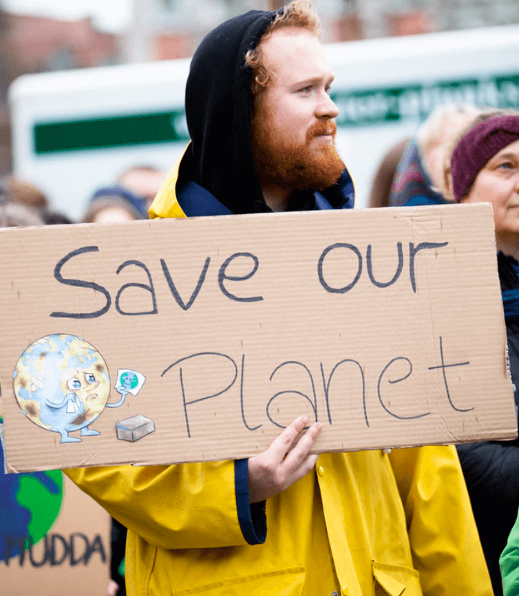 Ginger man in a yellow jacket holding a sign saying save our planet.