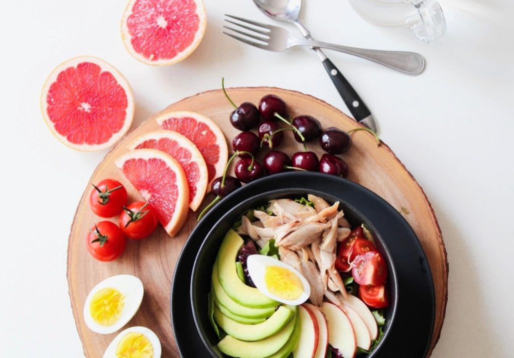 nicely presented healthy meal consisting of fruits, vegetables, eggs and meat.