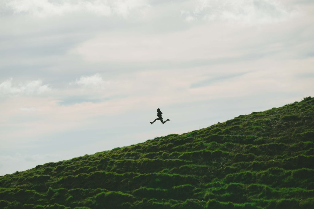 silhouette of person leaping down a grassy hill.