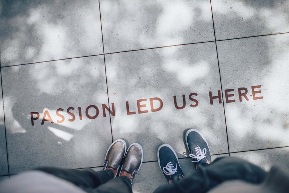 concrete floor with paint saying 'passion led us here'