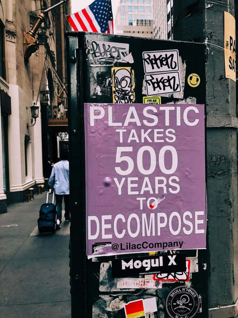 purple sign pasted on a black lamp post saying 'plastic takes 500 years to decompose'