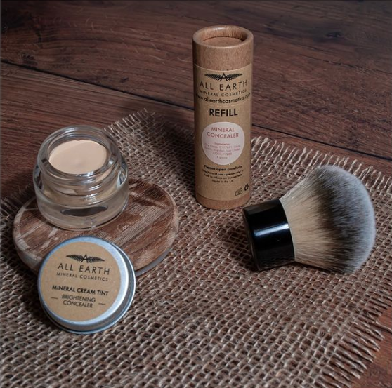 All Earth Mineral Cosmetics' mineral cream tint, concealer and brush on a rustic brown background.