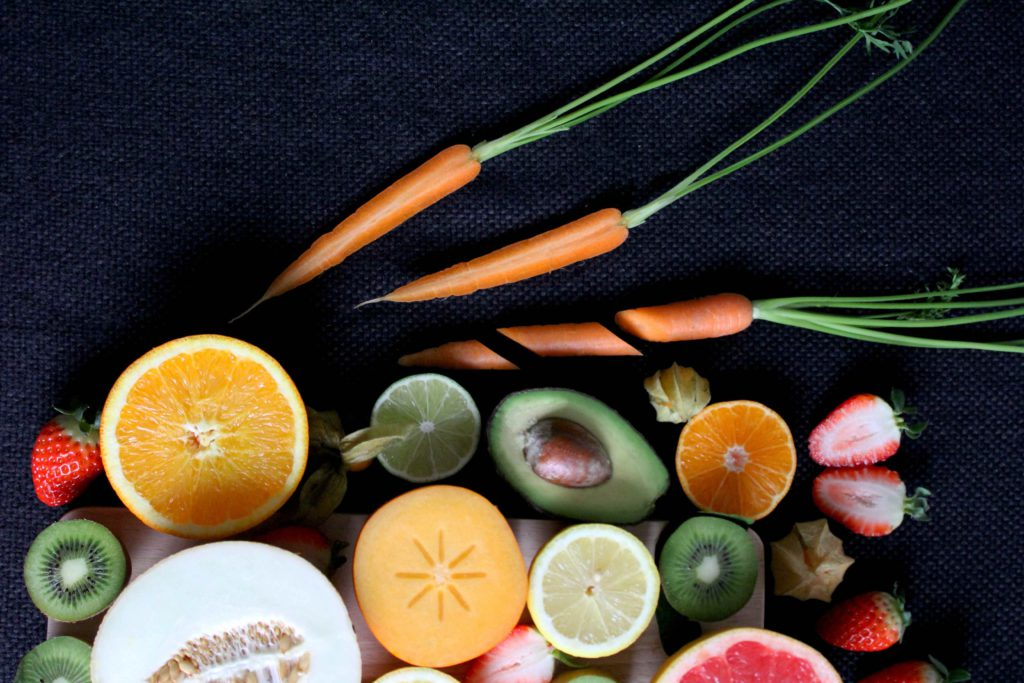 A selection of fruits and vegetables, including carrots, orange, melon, kiwi, avocado and strawberries against a black textured background.