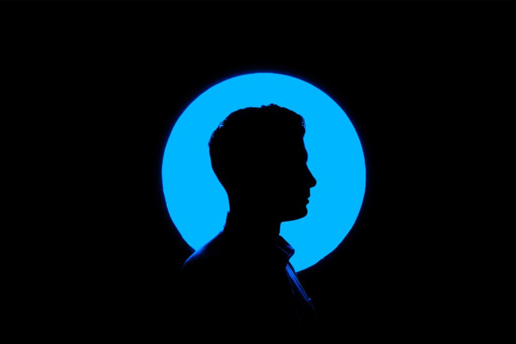 silhouette of a man against a circular blue light