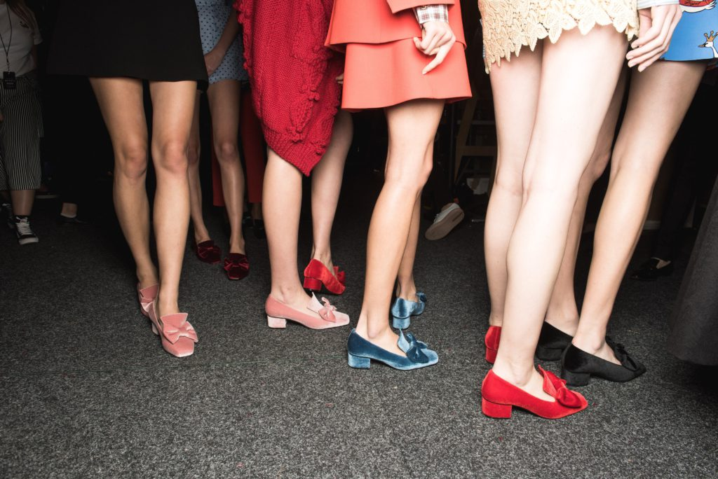 a group of models' legs with red, blue and pink suede shoes on.