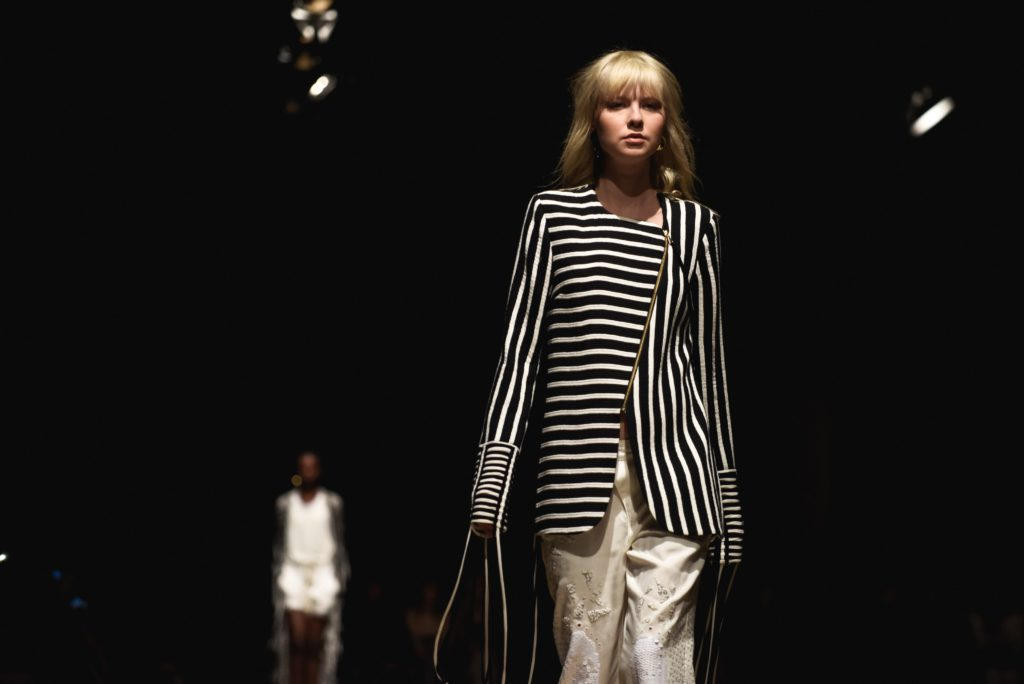 Fashion week showing a woman in a black and white striped jacket and white trousers.