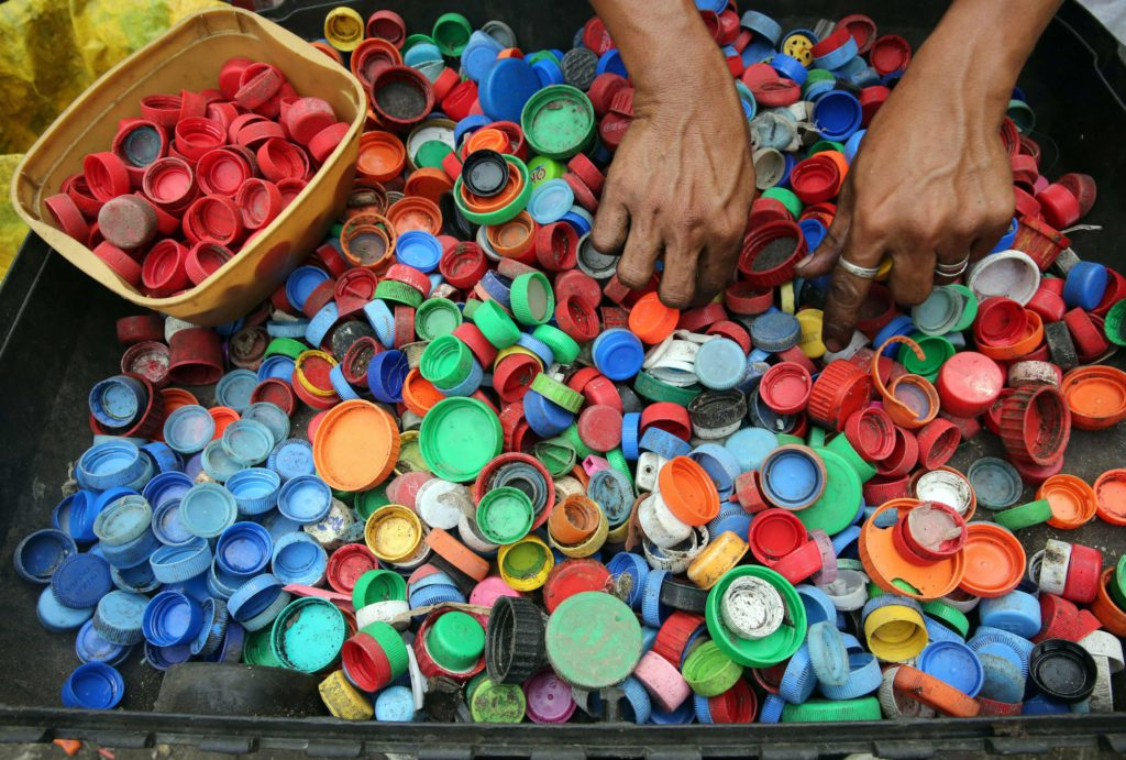 Hands sorting though hundreds of multi coloured bottle caps.