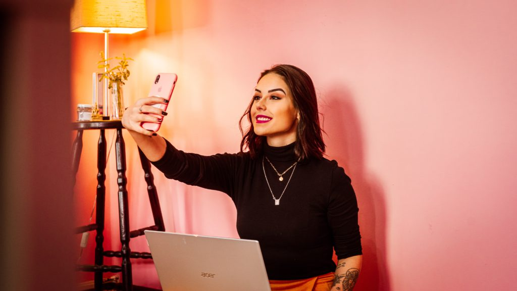 Female influencer with makeup on against a pink background taking a selfie.