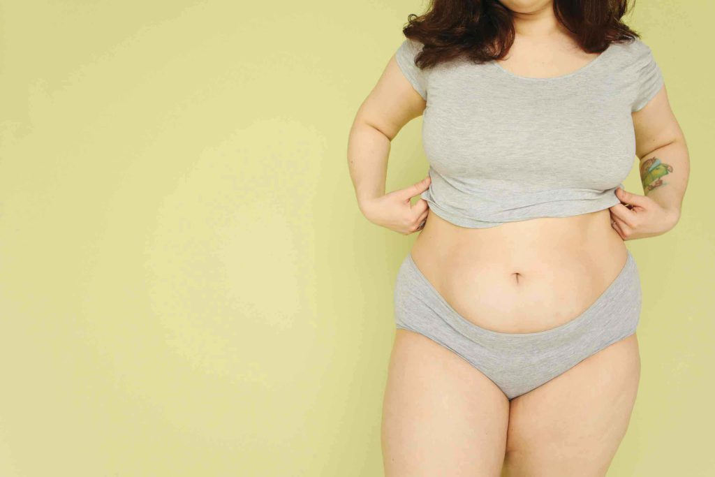 shapely woman in grey underwear against a greeny-yellow background showing that beauty comes in all shapes and sizes.