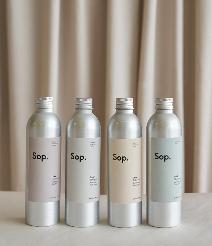 Sop shampoo, conditioner and body wash against a natural beige background